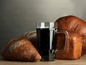 Tankard of kvass and rye breads, on wooden table on grey background — Stock Photo