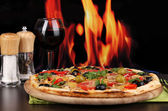 Delicious pizza with glass of red wine and spices on wooden table on fire background — Stock Photo