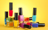 Group of bright nail polishes, on yellow background — Stock Photo