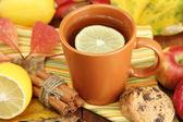 Tasse de thé chaud et des feuilles de l'automne, sur la table en bois — Photo