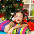 Little girl dreaming near christmas tree — Stock Photo #16270625