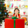 Little girl with large gift box near christmas tree — Stock Photo #16270627
