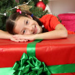 Little girl with large gift box near christmas tree — Stock Photo #16270631