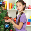 Little girl decorating christmas tree - Stockfoto
