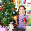 Little girl decorating christmas tree — Stockfoto