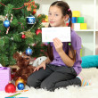 Little girl writing letter to Santa near christmas tree - Stock Photo