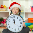 Little girl holding clock near christmas tree — Stock Photo #16270677