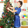 Little girl holding toy near christmas tree — Stock Photo #16270691