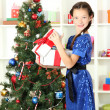 Little girl holding gift box near christmas tree — Stock Photo #16270701