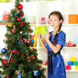 Little girl holding gift box near christmas tree — Stock Photo #16270705