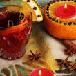 Fragrant mulled wine in glass with spices and oranges around on wooden table - Foto Stock
