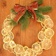Christmas wreath of dried lemons with fir tree and bow, on wooden background — 图库照片