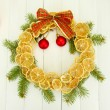 Christmas wreath of dried lemons with fir tree and balls, on wooden background — Photo