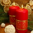 Two candles and christmas decorations, on golden background — Stock Photo #16270931
