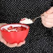 Young woman is eating cottage cheese with sliced strawberries — Stock Photo #16270963