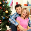 Young happy couple near a Christmas tree at home — Stock Photo #16271081