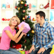 Young happy couple with presents sitting near Christmas tree at home — Stock Photo #16271119