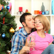 Young happy couple holding glasses with champagne near Christmas tree at home — Stock Photo
