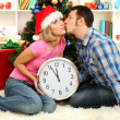 Young happy couple holding clock near Christmas tree at home — Stock Photo #16271143