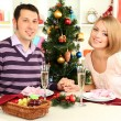 Young happy couple holding glasses with champagne at table near Christmas tree — Stock Photo #16271171