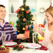 Young happy couple with presents sitting   at table near Christmas tree — Lizenzfreies Foto
