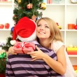 Young happy couple with presents sitting near Christmas tree at home — Stock Photo #16271211