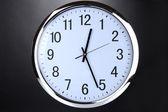 Round office clock on black background — Stock Photo