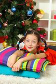 Little girl dreaming near christmas tree — Stock Photo