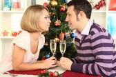 Jonge gelukkige paar bril met champagne bedrijf aan tafel in de buurt van de kerstboom — Stockfoto