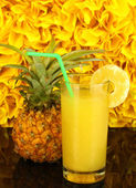 Ripe pineapple and juice glass on black table on yellow decorative background — Stock Photo