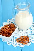 Sabrosas galletas en la jarra de leche y tazón de fuente blanca en primer plano de la mesa de madera — Foto de Stock