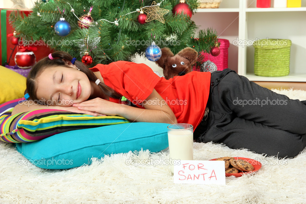 Little girl sleeping near christmas tree — Stock Photo #16270619