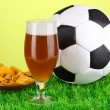Glass of beer with soccer ball on grass on green background — Stock Photo #16303063