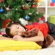 Stock Photo: Little girl sleeping near christmas tree