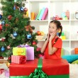 Little girl with large gift box near christmas tree — Stock Photo #16304109