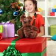 Little girl with large gift box near christmas tree — Stock Photo #16304127