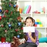 Little girl writing letter to Santa near christmas tree — Stock Photo