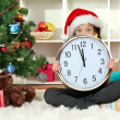 Little girl holding clock near christmas tree — Stock Photo #16304249