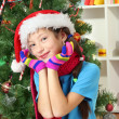 Little girl with pink scarf and multicolor gloves sitting near christmas tree — Stock Photo