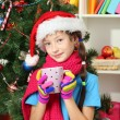Little girl with pink scarf and cup of hot drink sitting near christmas tree — Stock Photo #16304279