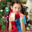 Little girl with pink scarf and glass of milk sitting near christmas tree — Stock Photo #16304289