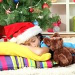 Little girl sleeping near christmas tree — Stock Photo #16304295
