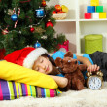 Little girl sleeping near christmas tree — Stock Photo