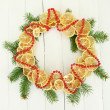 Christmas wreath of dried lemons with fir tree, on white wooden background — Photo