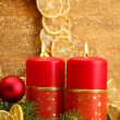 Two candles and christmas decorations, on golden background — Stock Photo #16304495