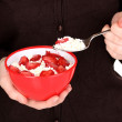 Stock Photo: Young woman is eating cottage cheese with sliced strawberries