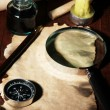 Old paper with ink pen and magnifying glass near lighting candle on wooden table — Stock Photo