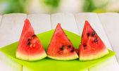Tranches de melon d'eau douce sur la plaque sur une table en bois sur fond naturel — Photo
