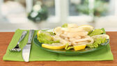 Cooked squid rings on lettuce with lemon on the plate close-up — Stock Photo