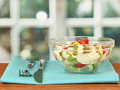 Squid salad with vegetables in a glass bowl on wooden table close-up — Stock Photo